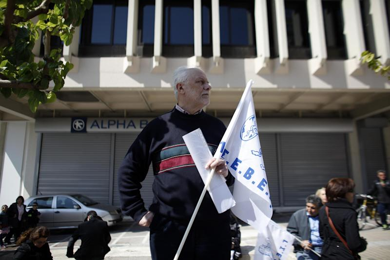 A protester holds a labor union flag during a protest from the confederation of Professionals, Craftsmen and Merchants against a new austerity bill that will be discussed in Parliament, in Athens, Sunday, March 30 2014. The measures demanded by bailout lenders will be voted on late Sunday, and would liberalize several retail sectors. They include plans to grant supermarkets permission to set up in-store pharmacies, scrap price limits on books and allow a longer shelf-life for milk. (AP Photo/Kostas Tsironis)