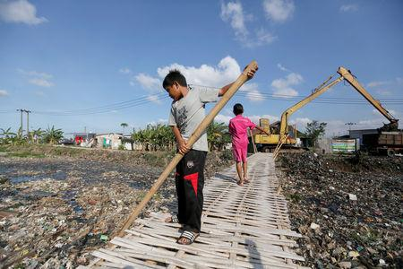 A boy uses a bamboo stick to clean a river covered by rubbish in Bekasi, West Java province, Indonesia, January 7, 2019. REUTERS/Willy Kurniawan/Files