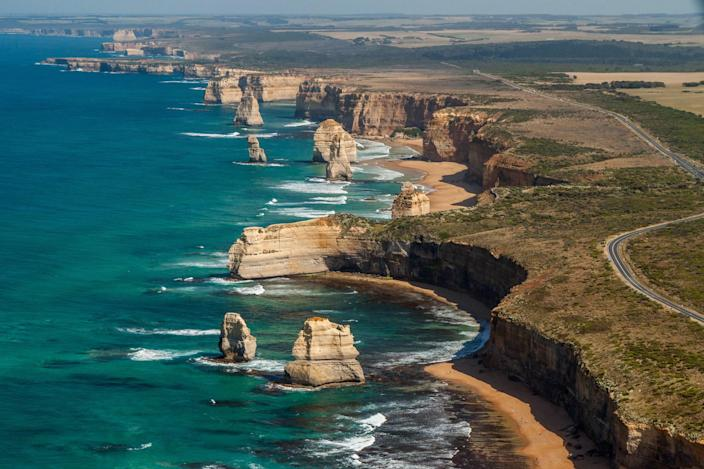 An aerial view of the collection of limestone stacked, more commonly known as The Twelve Apostles. The popular tourist attraction sits just south of the <strong>Great Ocean Road</strong> in Australia. Built in 1932, the 151 mile stretch of road hugs the southeastern coast of Australia.