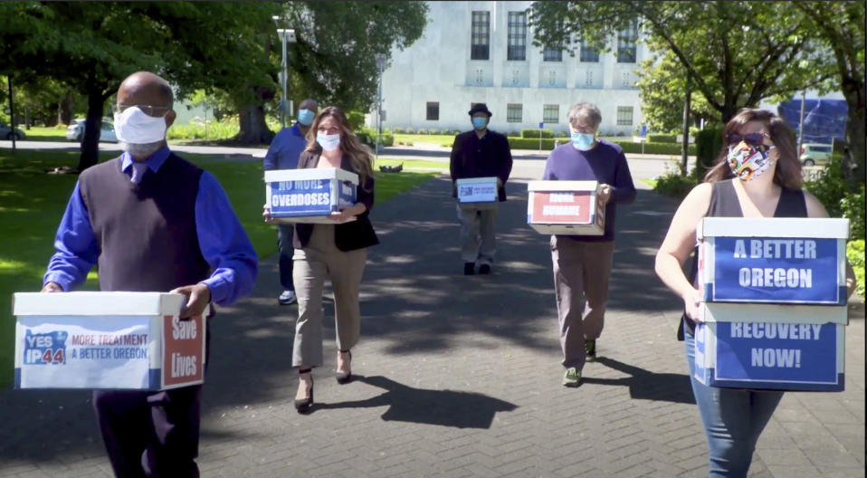FILE - In this June 26, 2020, file photo taken from video, provided by the Yes on Measure 110 Campaign, volunteers deliver boxes containing signed petitions in favor of the measure to the Oregon Secretary of State's office in Salem, Ore. The measure said the U.S., possession of small amounts of heroin, cocaine, LSD and other hard drugs would be decriminalized in Oregon. Police in Oregon can no longer arrest someone for possession of small amounts of heroin, methamphetamine and other hard drugs as the ballot measure that decriminalized them took effect on Monday, Feb. 1, 2021. (Yes on Measure 110 Campaign via AP, File)