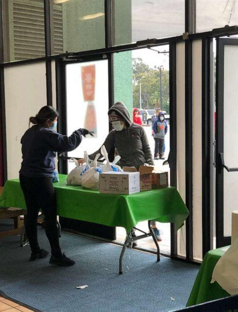 PHOTO: A staff member from Arts in Action Community Charter Schools in East Los Angeles hands out free packaged lunches the pandemic. (Stephanie Conde)