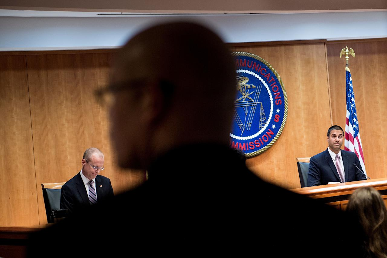 <p>FCC Commissioner Brendan Carr (L) and Chairman Ajit Pai listen during a hearing at the Federal Communications Commission on Dec. 14, 2017 in Washington. (Photo: Brendan Smialowski/AFP/Getty Images) </p>