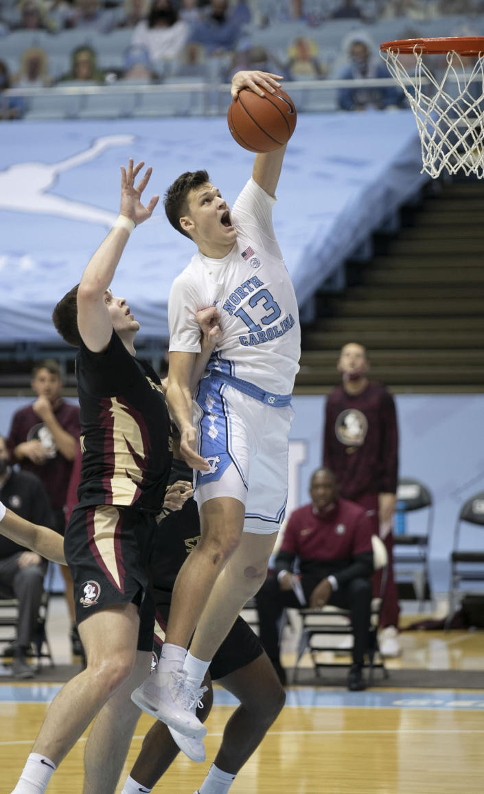 North Carolina's Walker Kessler (13) secures an offensive rebound over Florida State's Balsa Koprivica (5) during the first half on Saturday, Feb. 27, 2021, in Chapel Hill, N.C. (Robert Willett/The News & Observer via AP)