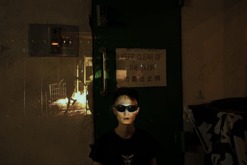 "A protester who identified himself as Eliot, 33, poses for a portrait as a projector displays a photograph, previously taken during the unrest, over him at a protest in Hong Kong. Eliot believes that his role in the protest is to protect the younger demonstrators, ""If it's necessary I can be arrested for them"" he says. (Photo: Felipe Dana/AP)"