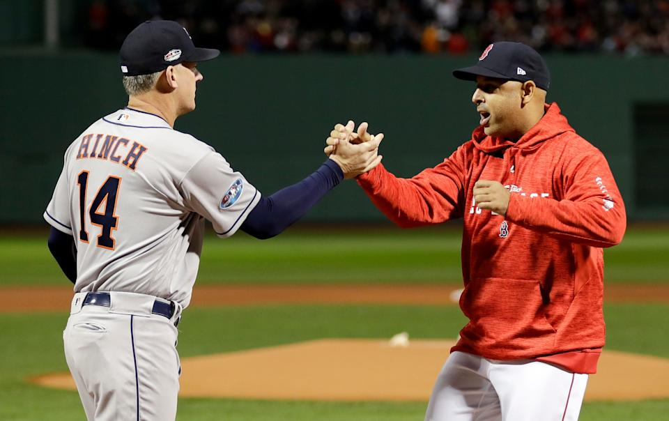 FILE - In this Oct. 13, 2018, file photo, Houston Astros manager AJ Hinch, left, and Boston Red Sox manager Alex Cora shake hands before Game 1 of a baseball American League Championship Series in Boston. Detroit Tigers general manager Al Avila said Friday, Oct. 2, 2020, that Detroit is not ruling out the possibility of hiring A.J. Hinch or Alex Cora for its managerial vacancy. Hinch and Cora were suspended this season for their roles in the Houston Astros' sign-stealing scandal. (AP Photo/David J. Phillip, File)