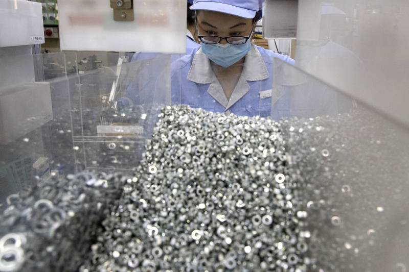 In this Wednesday, May 13, 2020 photo, a worker at SMC China, a Japanese joint venture pneumatic engineering company, assembles products at a factory in Beijing. The United States, Japan and France are prodding their companies to rely less on China to make the world's smartphones, drugs and other products. But even after the coronavirus derailed global trade, few are willing to give up access to its skilled workers, vast market and efficient suppliers by moving factories closer to home.(AP Photo/Ng Han Guan)