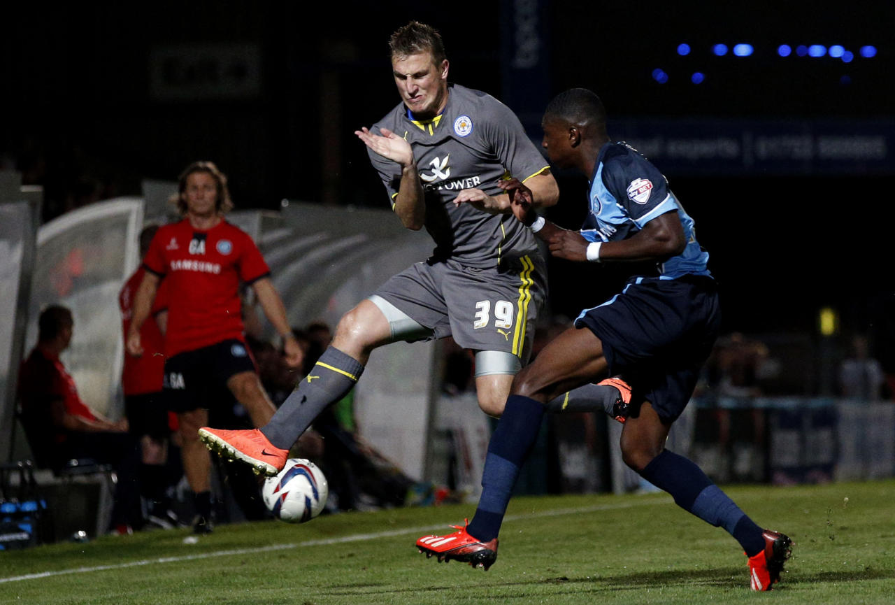Leicester's Chris Wood (left) braces himself in the air against the clearance from Wycombe's Kortney Hause (right) during the Capital One Cup, First Round match at Adams Park, Wycombe.