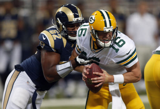 Green Bay Packers quarterback Scott Tolzien, right, is sacked for a 1-yard loss by St. Louis Rams defensive tackle Ethan Wesbrooks during the second quarter of an NFL preseason football game Saturday, Aug. 16, 2014, in St. Louis. (AP Photo/Scott Kane)