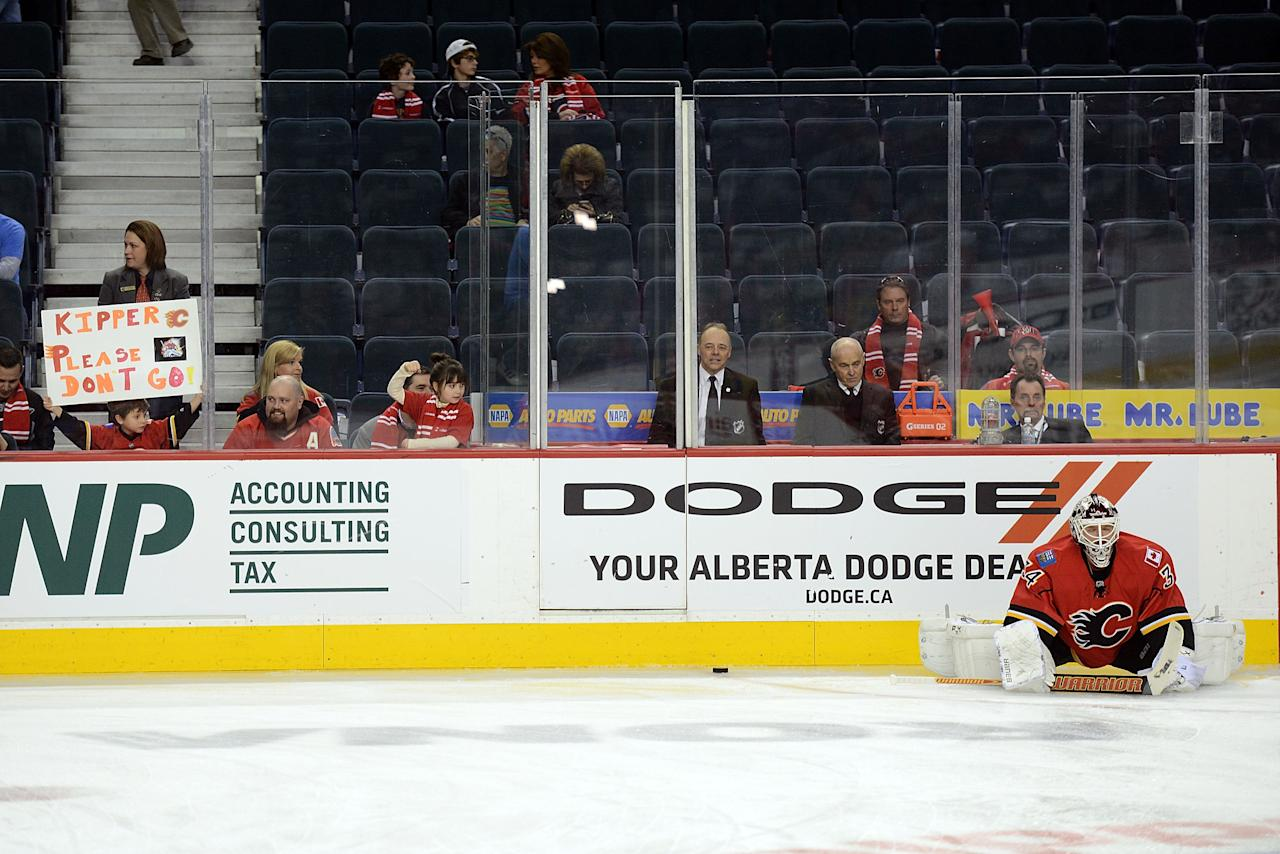 CALGARY, CANADA - APRIL 19: Miikka Kiprusoff #34 of the Calgary Flames stretches during the warmup while a fan holds up a sign in appreciation before the game against the Anaheim Ducks on April 19, 2013 at the Scotiabank Saddledome in Calgary, Alberta, Canada. (Photo by Terence Leung/NHLI via Getty Images)