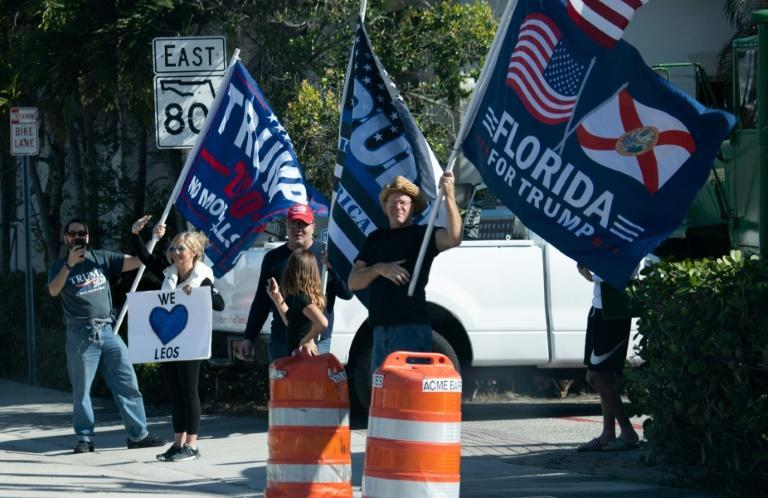 Supporters of US President Donald Trump, shown here cheering at his motorcade in West Palm Beach, Florida, on December 27, 2020, say his presence at his Mar-a-Lago resort has boosted the region's profile
