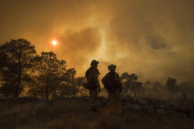 <p>CalFire firefighter Jake Hainey, left, and engineer Anna Mathiasen watch as a wildfire burns near Oroville, Calif., on Saturday, July 8, 2017. The fast-moving wildfire in the Sierra Nevada foothills destroyed structures, including homes, and led to several minor injuries, fire officials said Saturday as blazes threatened homes around California during a heat wave. (AP Photo/Noah Berger) </p>