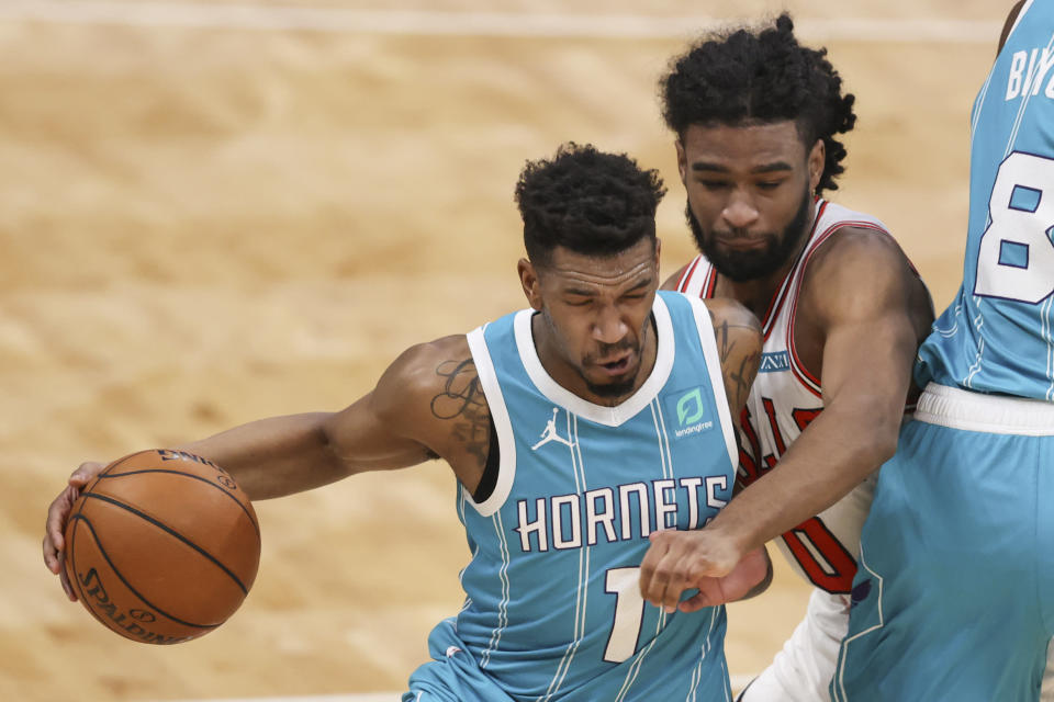 Charlotte Hornets guard Malik Monk, left, drives against Chicago Bulls guard Coby White during the first half of an NBA basketball game in Charlotte, N.C., Thursday, May 6, 2021. (AP Photo/Nell Redmond)