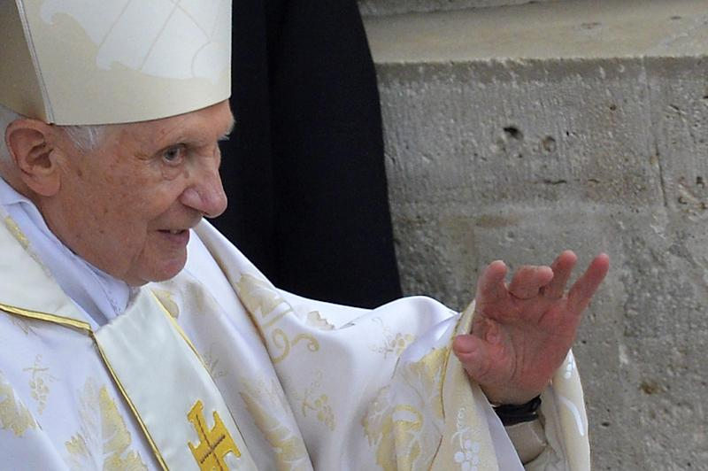Pope emeritus Benedict XVI waves as he arrives at the Vatican on April 27, 2014