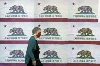 FILE - In this Thursday, April 30, 2020, file photo, a pedestrian wearing a mask walks in front of a billboard displaying California flags in San Francisco during the coronavirus outbreak. California's death count from the coronavirus surpassed 15,000 on Sunday, Sept. 20, 2020 even as the state saw widespread improvement in infection levels. (AP Photo/Jeff Chiu, File)