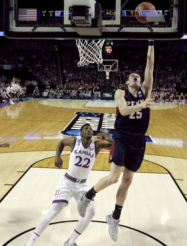 Pennsylvania forward AJ Brodeur (25) gets past Kansas forward Silvio De Sousa (22) to put up a shot during the first half of an NCAA college basketball tournament first-round game Thursday, March 15, 2018, in Wichita, Kan. (AP Photo/Charlie Riedel)