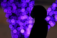 A woman wears masks to prevent the spread of the coronavirus as she looks at a holiday display on a mild day Saturday, Dec. 26, 2020, in a park in Lenexa, Kan. (AP Photo/Charlie Riedel)