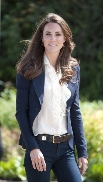 <p>In July 2011, Kate Middleton topped denim and a frilly blouse with a classic navy blazer while visiting a town devastated by a fire a few months before. </p>