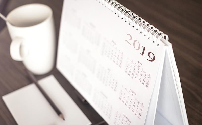 A 2019 calendar beside a mug on a desk.