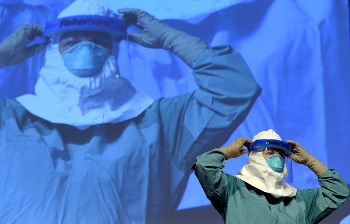 Barbara Smith from Mount Sinai Health Systems demonstrates the proper technique for donning protective gear during an Ebola educational session for healthcare workers at the Jacob Javits Center in New York on October 21, 2014 (AFP Photo/Timothy A. Clary)