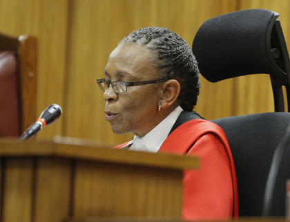 Judge Thokozile Masipa reads her verdict as Oscar Pistorius sits in the dock. (AFP)
