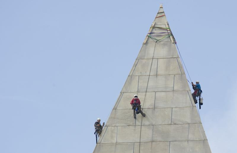 Construction workers rappel from the top of the Washington Monument in September 2011 in order to look for cracks sustained in the 5.8-magnitude earthquake one month earlier.