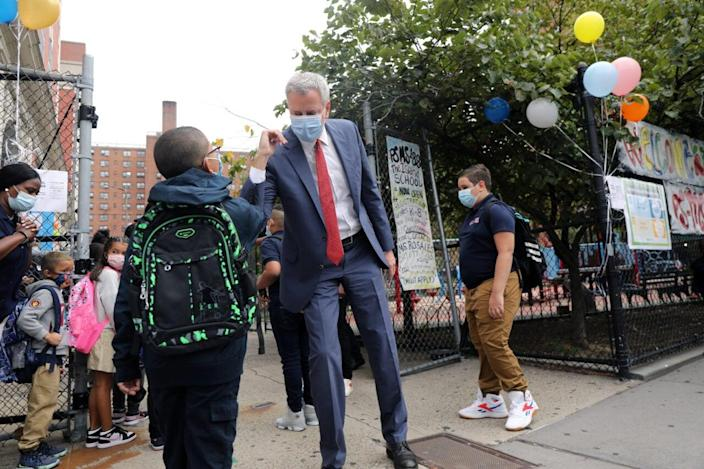 New York City Mayor Bill de Blasio elbow bumps a student at P.S. 188 as he welcomes elementary school students back to the city's public schools for in-person learning on September 29, 2020 in New York City. (Photo by Spencer Platt/Getty Images)