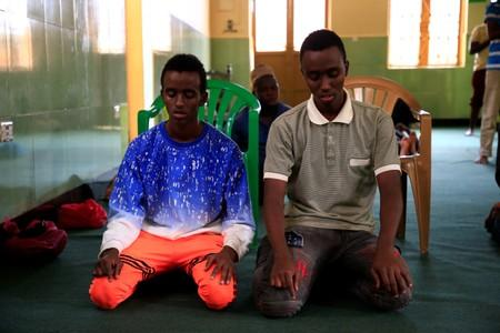 Somali refugees Abdullahi Mohamad (17) and his brother Abdirahman Mohamad (19) pray at a mosque in the Kisenyi neighbourhood in Kampala