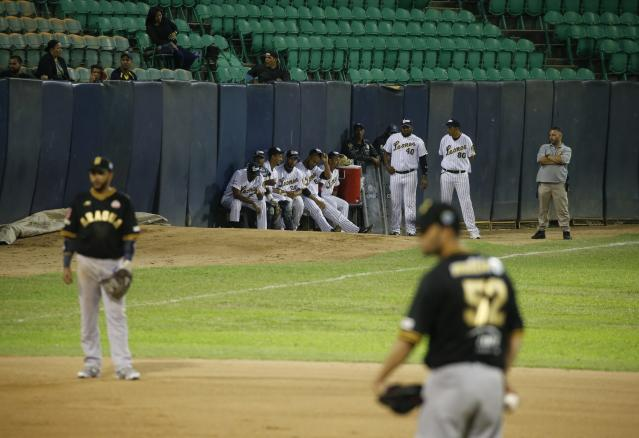 Leones de Caracas players watch the opening winter season baseball game against Tigres de Aragua in Caracas, Venezuela, Tuesday, Nov. 5, 2019. Tough times have shortened the season by a third of its games and it started weeks late. (AP Photo/Ariana Cubillos)