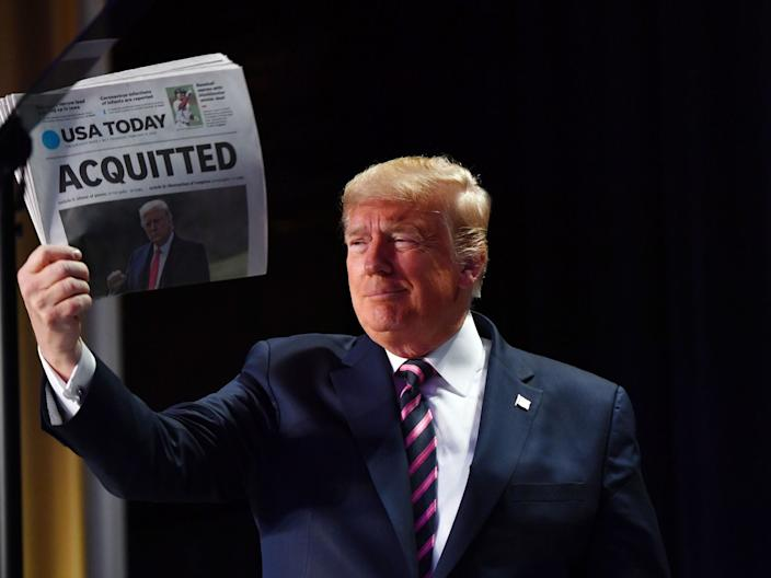 President Donald Trump holds up a newspaper that displays a headline