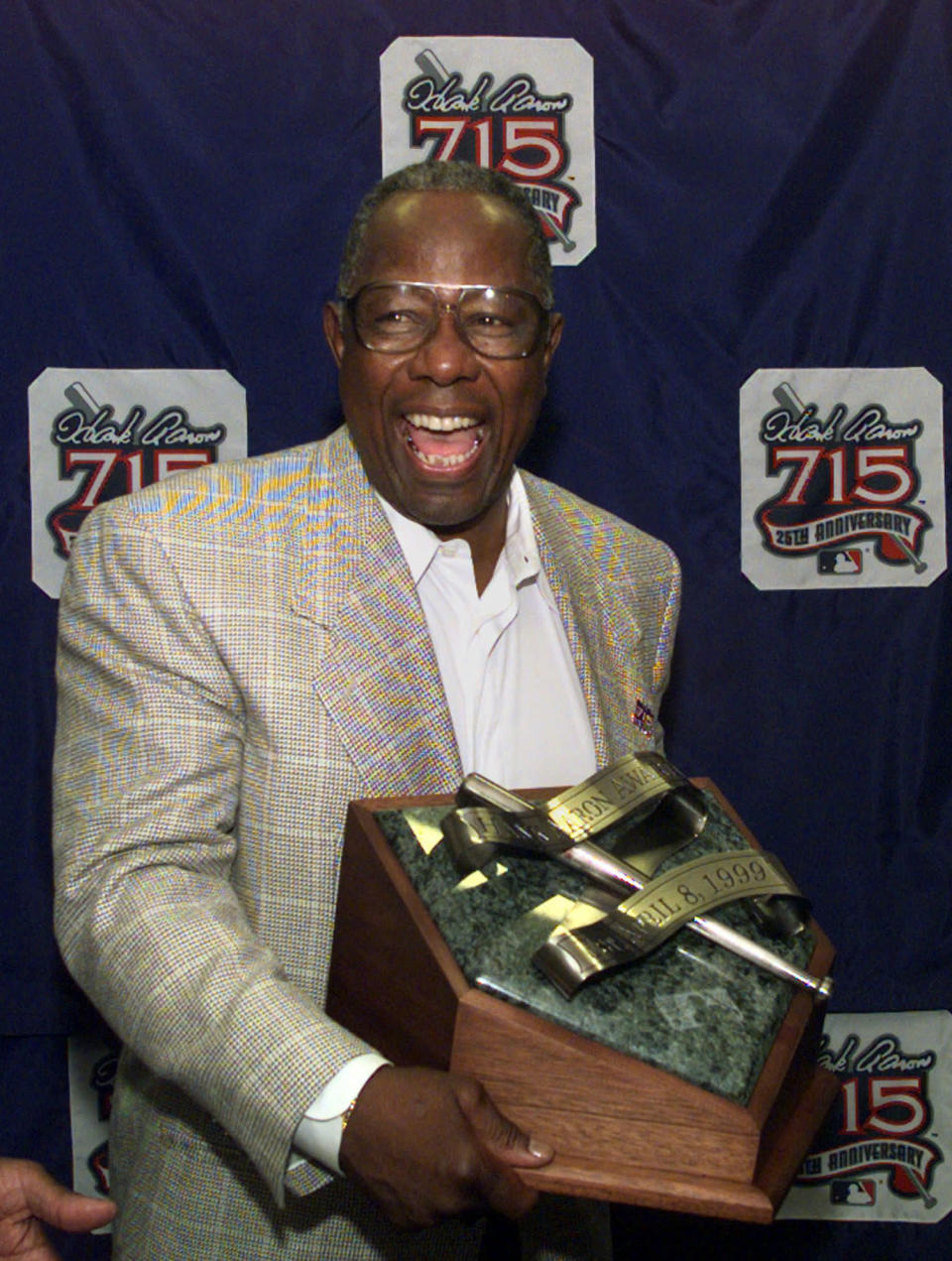 """FILE - In this April 8, 1999, file photo, Major League Baseball's all-time career home run record holder Hank Aaron laughs as he shows off the newly unveiled """"Hank Aaron Award"""" during a news conference in Atlanta. Hank Aaron, who endured racist threats with stoic dignity during his pursuit of Babe Ruth's home run record and gracefully left his mark as one of baseball's greatest all-around players, died Friday. He was 86. The Atlanta Braves, Aaron's longtime team, said he died peacefully in his sleep. No cause was given. (AP Photo/John Bazemore, File)"""