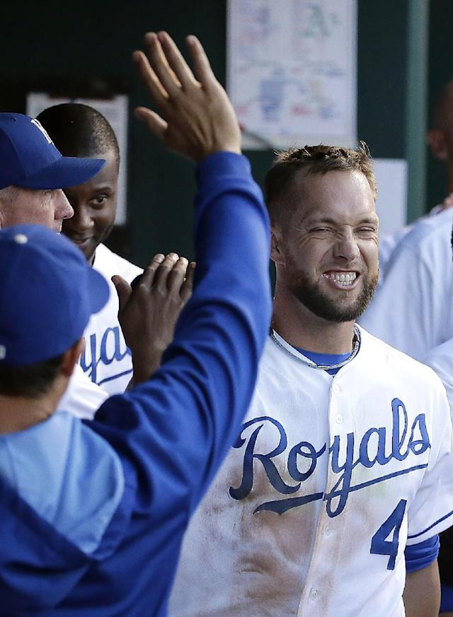 Kansas City Royals' Alex Gordon celebrates in the dugout after scoring on a single by Alcides Escobar during the second inning of a baseball game against the Oakland Athletics, Monday, Aug. 11, 2014, in Kansas City, Mo. (AP Photo/Charlie Riedel)