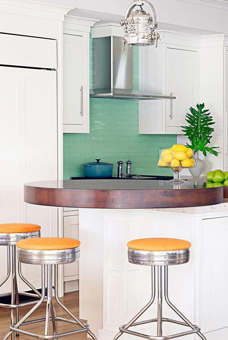 <p>High-gloss mint green tiles create a dramatic focal point in this white kitchen.</p>