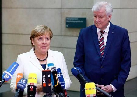 Christian Social Union (CSU) leader Horst Seehofer and Angela Merkel, leader of the Christian Democratic Union (CDU) talk to the media as they arrive at the German Parliamentary Society offices before the start of exploratory talks about forming a new coalition government in Berlin, Germany, October 20, 2017. REUTERS/Axel Schmidt