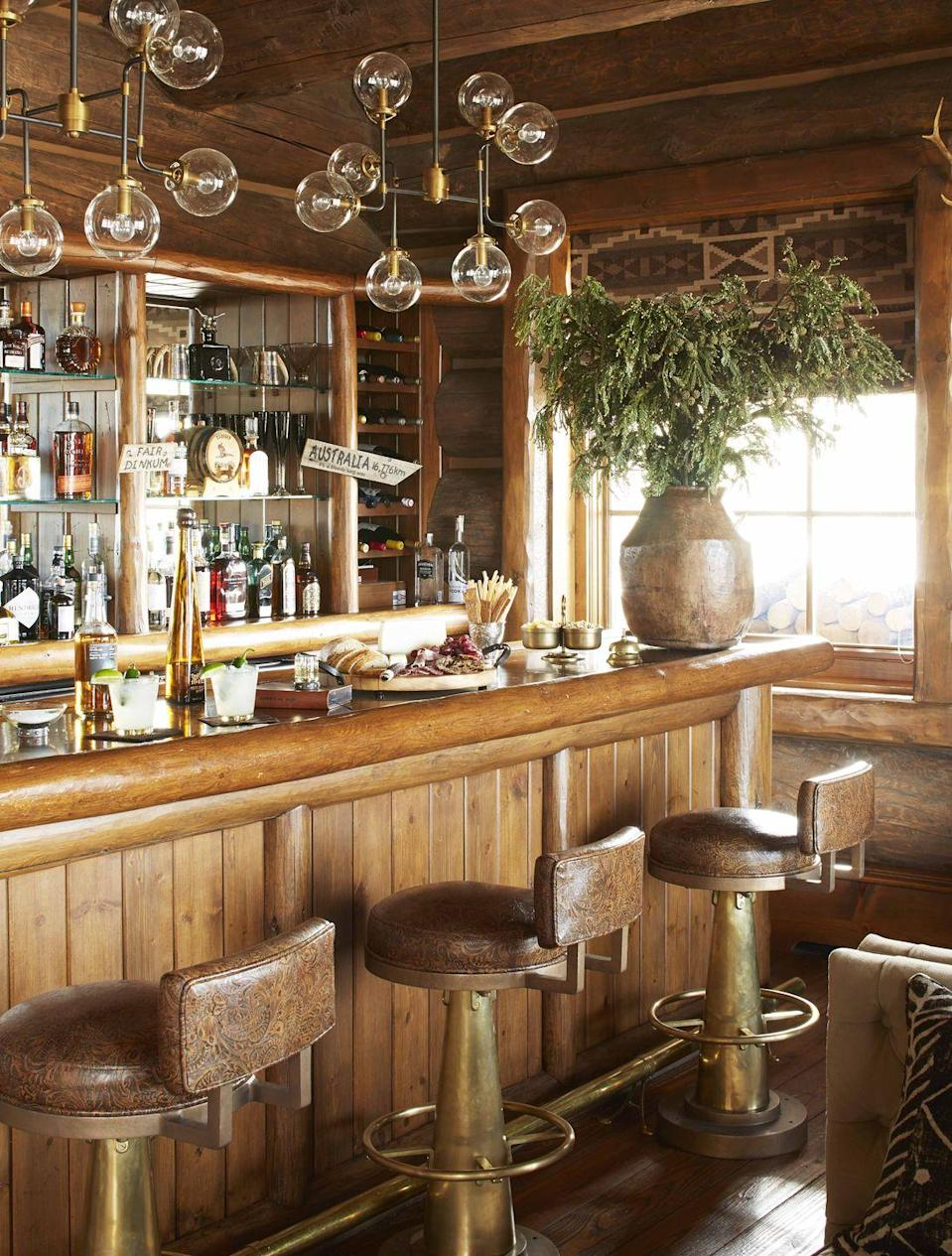 """<p>At their Colorado ranch, pro golfer Greg Norman and his wife Kirsten, an interior designer, end their horseback riding and snowmobiling-filled days with drinks at their cozy bar. A pair of industrial pendants provide sleek contrast to the log walls and bar. The <a href=""""https://www.gilanifurniture.com/"""" rel=""""nofollow noopener"""" target=""""_blank"""" data-ylk=""""slk:Gilani"""" class=""""link rapid-noclick-resp"""">Gilani</a> barstools are covered in a tooled leather by the Ranch Home Outfitters. </p><p><a class=""""link rapid-noclick-resp"""" href=""""https://go.redirectingat.com?id=74968X1596630&url=https%3A%2F%2Fwww.etsy.com%2Flisting%2F785290084%2Fvintage-condiment-server-caddy-bar%3Fgpla%3D1%26gao%3D1&sref=https%3A%2F%2Fwww.veranda.com%2Fdecorating-ideas%2Fg28837805%2Fhome-bar-ideas%2F"""" rel=""""nofollow noopener"""" target=""""_blank"""" data-ylk=""""slk:Find Similar Vintage Bar Snack Caddies Here"""">Find Similar Vintage Bar Snack Caddies Here</a></p>"""