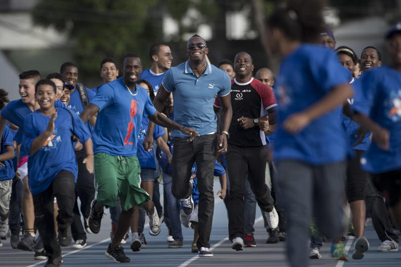 Jamaican Olympic gold medalist Usain Bolt, center, and sprinter Daniel Bailey, from Antigua and Barbuda, center left, run with young athletes during their visit to the Projeto Futuro Olimpico or Olympic Future Project in Rio de Janeiro, Brazil, Thursday, March 28, 2013. The Olympic Future Project promotes the practice of sports and healthy living, targeting the low-income populations of the inner city. (AP Photo/Felipe Dana)