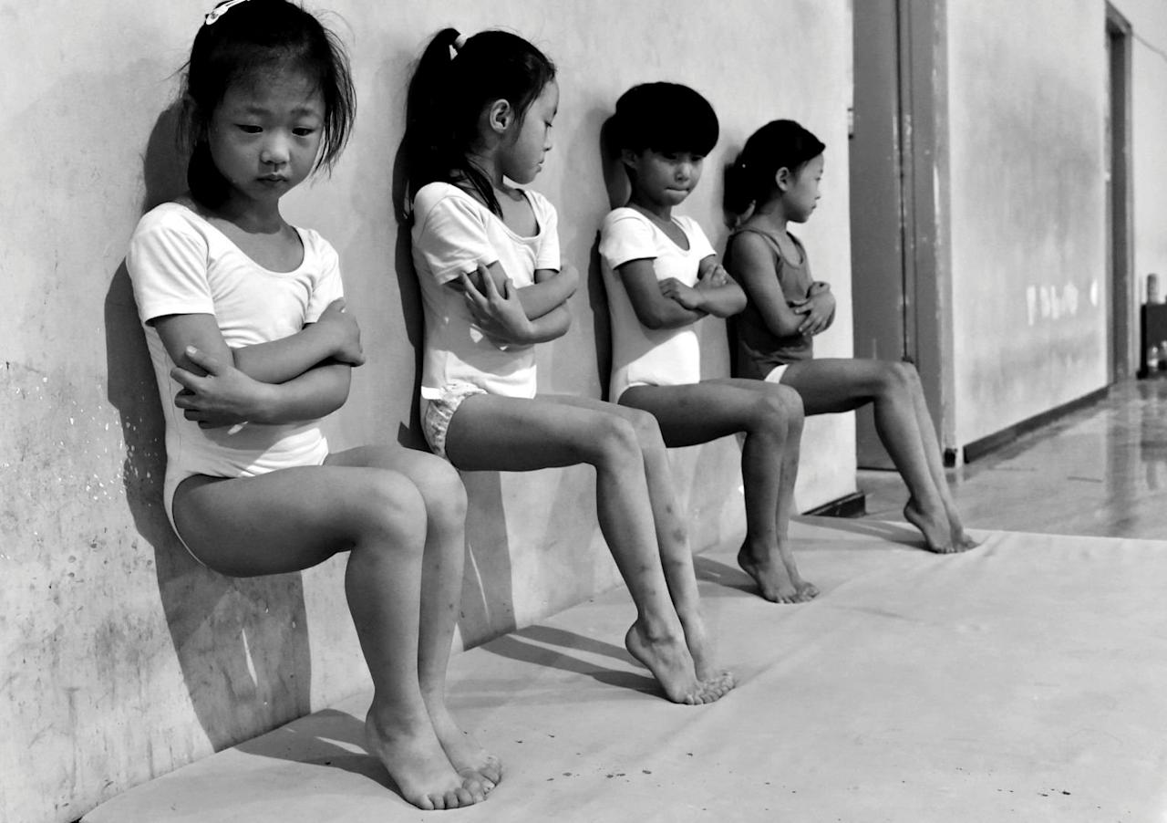 Four students of a gymnastics school in Xuzhou, China, do toe-pressure training for 30 minutes in the afternoon. Tiejun Wang/Courtesy of World Press Photo Foundation/Handout via REUTERS   THIS IMAGE HAS BEEN SUPPLIED BY A THIRD PARTY. FOR EDITORIAL USE ON WORLD PRESS PHOTO ONLY. NO RESALES. MANDATORY CREDIT. NO CROPPING
