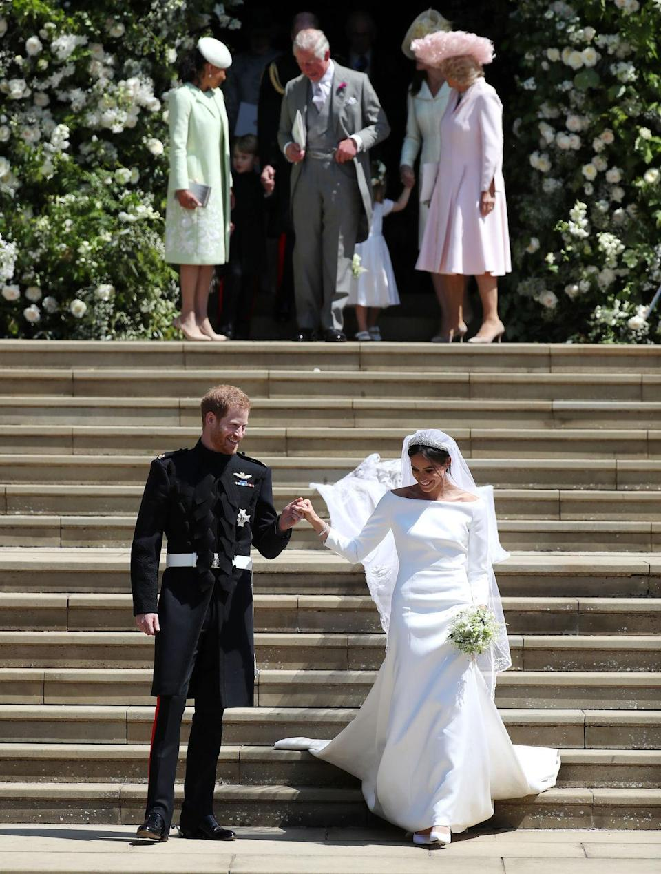 Prince Harry and Meghan Markle followed by (left-right back) Doria Ragland, mother of the bride, the Prince of Wales and the Duchess of Cornwall, after the ceremony. (Getty)