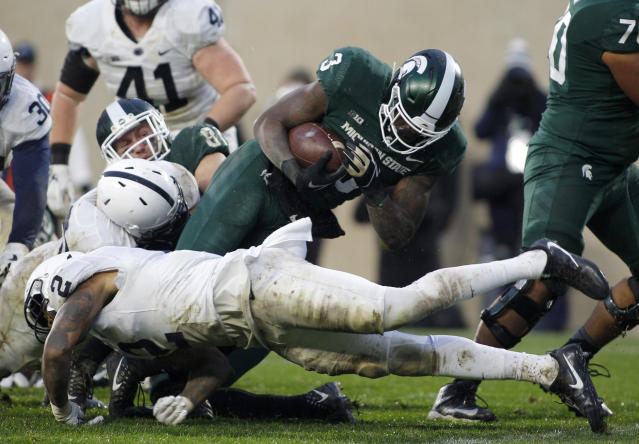 Michigan State running back LJ Scott (3) dives over Penn State's Marcus Allen (2) for a touchdown during the second half of an NCAA college football game, Saturday, Nov. 4, 2017, in East Lansing, Mich. (AP Photo/Al Goldis)