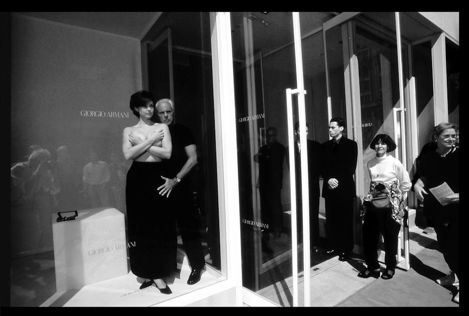 Giorgio Armani and Ashley Judd in the window of the Armani boutique on Madison Avenue in New York. Photographed for U.S. Vogue.