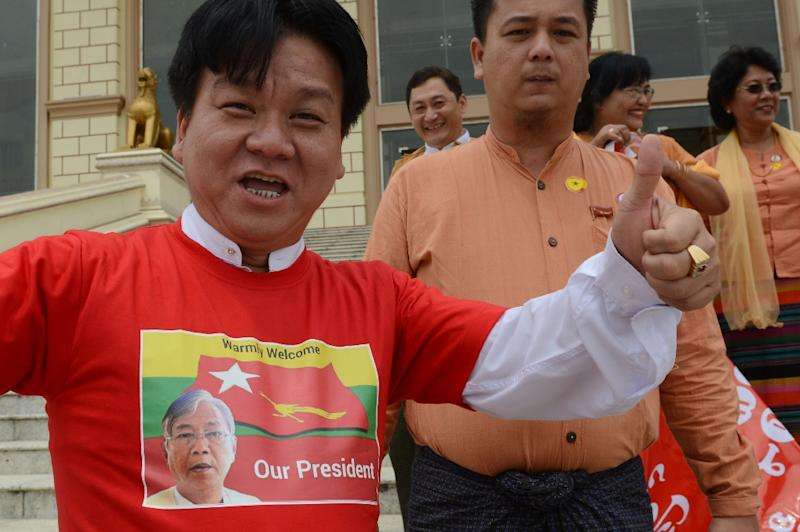 Party members of the National League for Democracy party celebrate in front of the parliament building after the swearing in ceremony of new Myanmar President Htin Kyaw in Naypyidaw on March 30, 2016