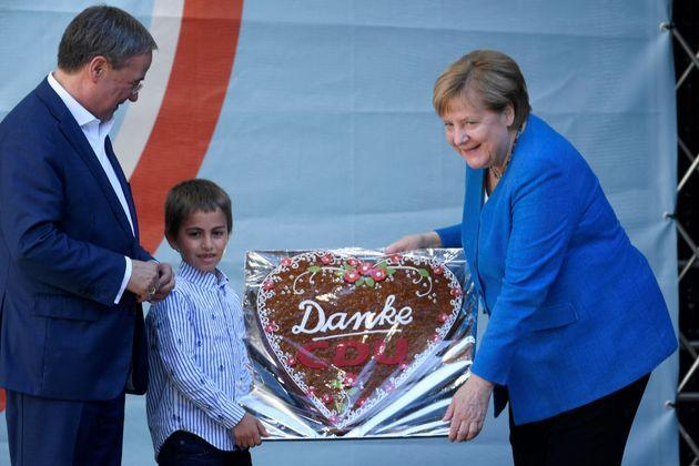 German Chancellor Angela Merkel (R) is presented with a gingerbread heart with the lettering 'Thank you CDU' during a campaign rally for Christian Democratic Union CDU leader and chancellor candidate Armin Laschet (L) in Aachen, western Germany, on September 25, 2021, one day ahead of the German federal elections. (Photo by Ina Fassbender / AFP) (Photo by INA FASSBENDER/AFP via Getty Images) (Photo: INA FASSBENDER via Getty Images)