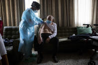 Nurse Pilar Rodríguez administers the COVID-19 vaccine to her patient Rafael Capo Frau, 92, at his home in the town of Sa Pobla on the Spanish Balearic Island of Mallorca, Spain, Friday, April 30, 2021. Spain has set the goal of vaccinating 70% of its adult population - some 33 million people - by the end of August. After being slowed by delays in shipments by drug makers, Spain has sped up its vaccination efforts and now has at least one shot in 12 million people. (AP Photo/Francisco Ubilla)