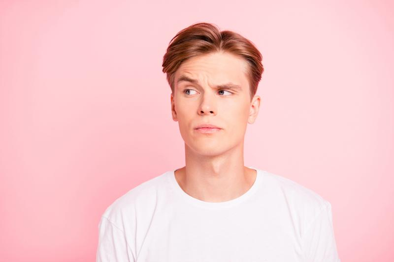 Man in white t-shirt against pink background raising an eyebrow