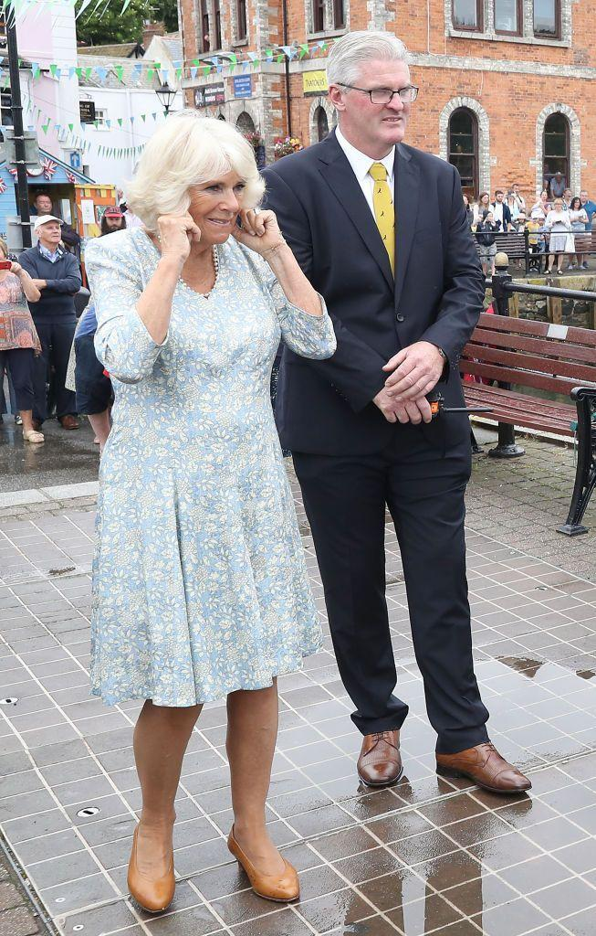 <p>Camilla Parker Bowles wore a light blue knee-length dress to a rowing race at the Fowey Festival Celebration in July 2018. She's shown here covering her ears as a small cannon is fired to mark the start of the event. </p>