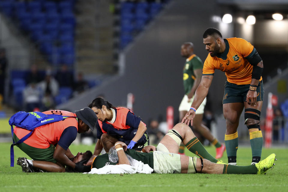 Australia's Samu Kerevi, right, checks on South Africa's Lood de Jager, bottom, as he is attended to by medical staff during their Rugby Championship match on Sunday, Sept. 12, 2021, Gold Coast, Australia. (AP Photo/Tertius Pickard)