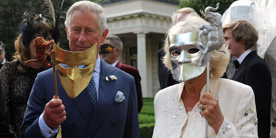 <p>Prince Charles and Camilla hold up metallic animal masquerade masks while at a charity event in London.</p>