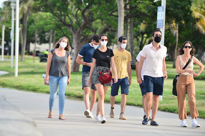 People seen walking on the beach side walk some wearing mask and some not wearing a face mask on July 06, 2020 in Miami Beach, Florida. Miami Beach has mandated that masks be worn in public, where social distancing is not possible. (Johnny Louis/Getty Images)