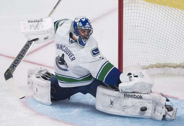 Vancouver Canucks goaltender Roberto Luongo makes a save against the Montreal Canadiens during the second period of an NHL hockey game Thursday, Feb. 6, 2014, in Montreal. (AP Photo/The Canadian Press, Graham Hughes)