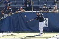 New York Yankees' Mike Tauchman, left, and Brett Gardner, second from left, watch as Gio Urshela bats in the cage during a baseball summer training camp workout Sunday, July 5, 2020, at Yankee Stadium in New York. (AP Photo/Kathy Willens)