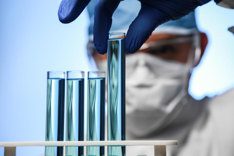 Scientists picking up a test tube from a rack of test tubes